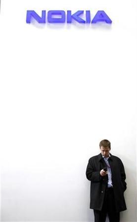 A visitor checks a mobile phone under a Nokia logo at Mobile World Congress in Barcelona