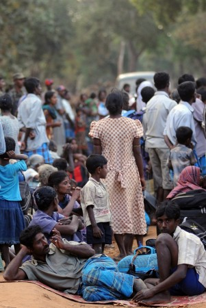Ethnic Tamil civilians wait to go to a camp for internally displaced people