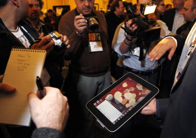 A man displays an unannounced Lenovo tablet computer at a preview of the CES in Las Vegas.