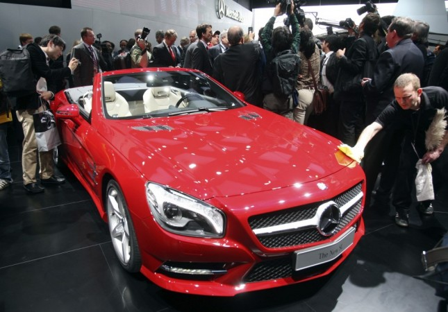 A worker removes fingerprints from the 2013 Mercedes Benz SL on the first press preview day at the North American International Auto Show in Detroit, Michiganon the first press preview day in Detroit, Michigan, January 9, 2012.