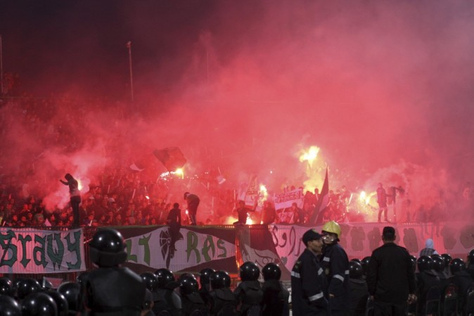 Police officers react as chaos erupts at a soccer stadium in Port Said city