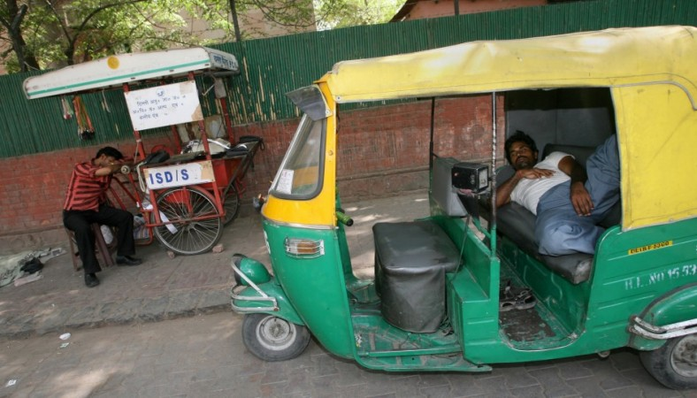 An auto-rickshaw driver taking a nap