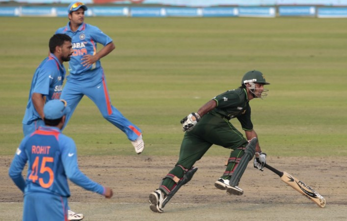 Pakistan's Mohammad Hafeez runs between the wickets as India's players watch during their One Day International (ODI) cricket match of Asia Cup in Dhaka.