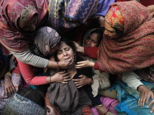 Unidentified women console the wife of Subhash Tomar  during his funeral in New Delhi.