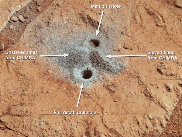 This image shows the first holes into rock drilled by NASA's Mars rover Curiosity, with drill tailings around the holes plus piles of powdered rock collected from the deeper hole and later discarded after other portions of the sample had been deliver