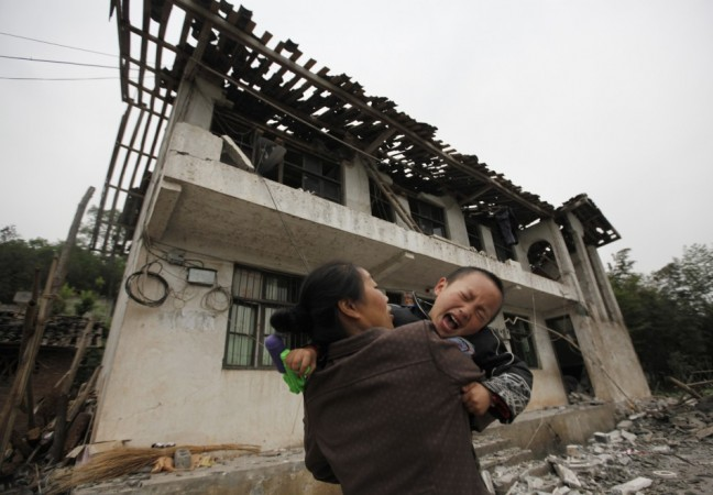 A boy cries as his mother holds him in front of their damaged house after a strong 6.6 magnitude earthquake at Longmen village, Lushan county in Ya'an, Sichuan province April 21, 2013.