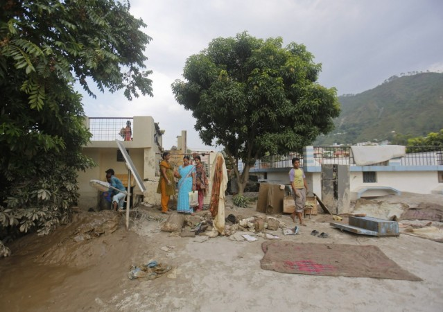 Residents take out their personal belongings from houses submerged in sand due to floods in Srinagar in the Himalayan state of Uttarakhand June 19, 2013.