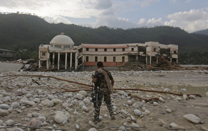 A member of the rescue operation team of Sashastra Seema Bal (SSB) or Armed Border Force walks towards the officers training centre damaged by floods at their campus in Srinagar in the Himalayan state of Uttarakhand June 19, 2013.