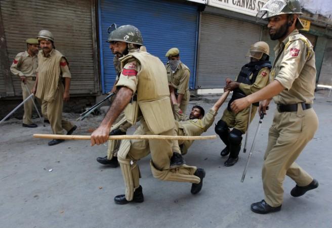 Indian policemen carry their injured colleague after he was wounded during a protest in Srinagar July 18, 2013.