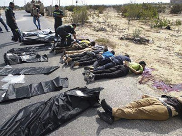 Army soldiers and medical workers check the bodies of police officers killed early morning on the highway in Rafah city