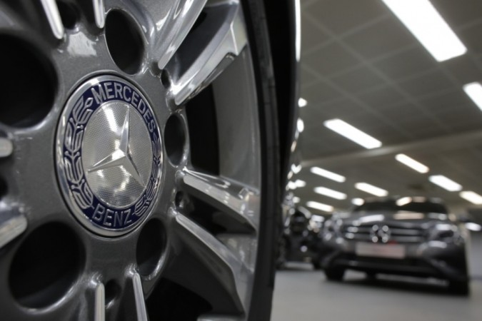 A company logo is seen on a wheel in front of Mercedes-Benz A-class cars displayed in a dealership of German car manufacturer Daimler in Paris (Reuters)