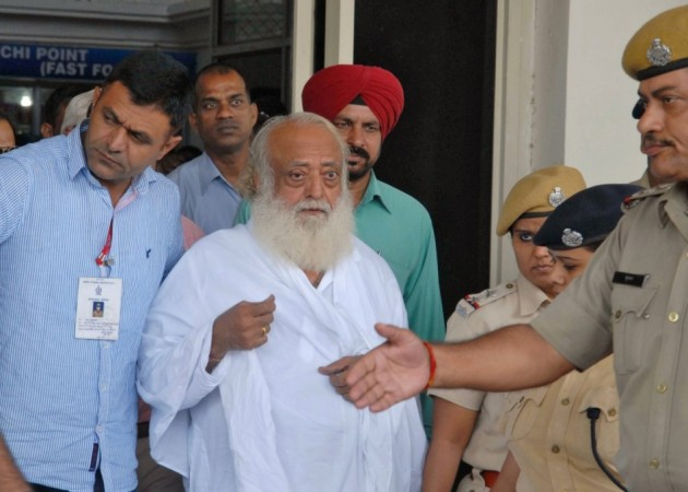 Police escort spiritual leader Asaram Bapu (C) outside an airport after his arrest in Jodhpur. (Reuters)