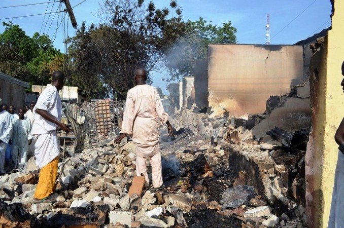 Residents Watch as Two Men Walk Amidst Rubble After Boko Haram Militants Raided the Town of Benisheik, West of Borno State Capital Maiduguri