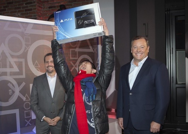 A Proud owner flaunts his Sony PlayStation 4 with Jack Tretton (R), President and CEO of SCE America, 2013