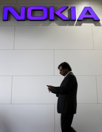File picture shows a man walking past a Nokia logo during the Mobile World Congress in Barcelona February 28, 2012.