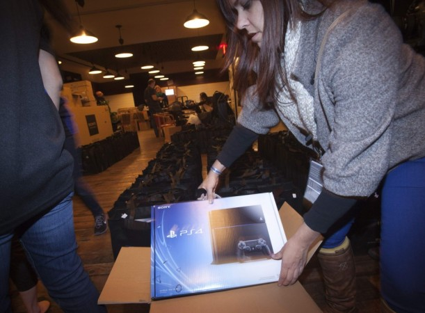 A Sony employee takes a Playstation 4 out of the box in advance of a special sale event put on by Sony at the Standard Hotel in New York