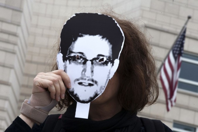 A woman holds a portrait of former US spy agency contractor Edward Snowden in front of her face as she stands in front of the US embassy during a protest in Berlin.