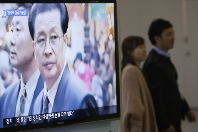 A couple walks past a television showing a report on Chang Song-thaek, North Korean leaders' uncle, at a railway station in Seoul (Reuters)