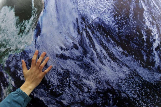 An environmental activist places his hand on a giant globe in a rally demanding more action to battle climate change during the 19th conference of the United Nations Framework Convention on Climate Change (COP19) in Warsaw November 16, 2013.