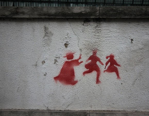 Graffiti on a wall in Lisbon depicting a priest chasing two children, denouncing the child abuse scandal that rocked the catholic church (which is still quite powerful in Portugal). Image taken 2 feb 2011/Creative Commons
