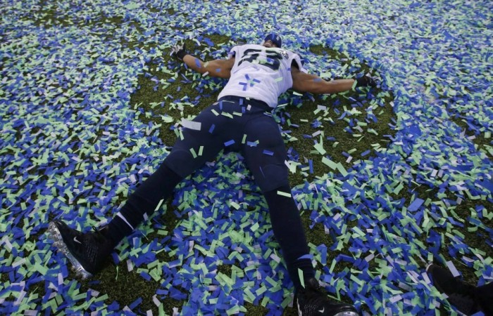 Seattle Seahawks Malcom Smith makes an angel in the confetti after his team defeated the Denver Bronocs in the NFL Super Bowl XLVIII football game in East Rutherford, New Jersey, February 2, 2014. REUTERS/Shannon Stapleton