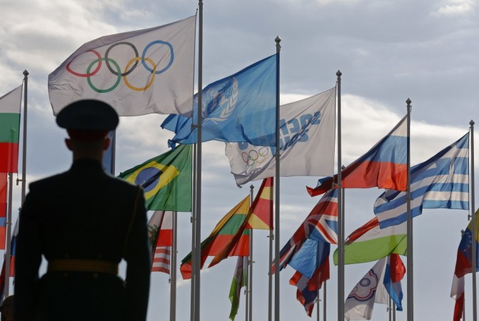 A Russian soldier stands in front of the flags during the welcoming ceremony for the U.S Olympic team in the Athletes Village at the Olympic Park ahead of the 2014 Winter Olympic Games in Sochi February 6, 2014.  REUTERS/Laszlo Balogh