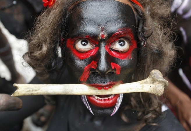A man dressed as a demon performs with a bone during a religious procession at the Mahashivratri festival in the northern Indian city of Allahabad February 27, 2014.
