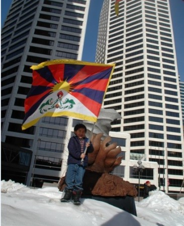 A Tibetan child waves the Tibetan national flag in front of a Twin-tower in Minneapolis, Minnesota, U.S.A. (Photo Credit: Tendar Tsering)