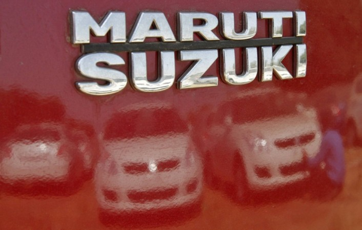 A worker cleans a Maruti Suzuki Swift Dzire car as he is reflected in a car at the company's stock yard at Sanand in Gujarat