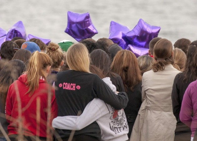 People gather at the beach for a vigil in honor of slain student Maren Sanchez in Milford