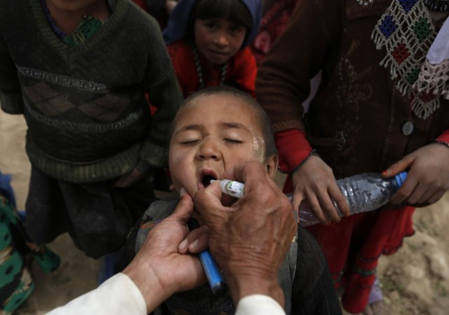 An Afghan child receives polio vaccination drops near the site of a landslide at the Argo district in Badakhshan province May 4, 2014. REUTERS/Mohammad Ismail