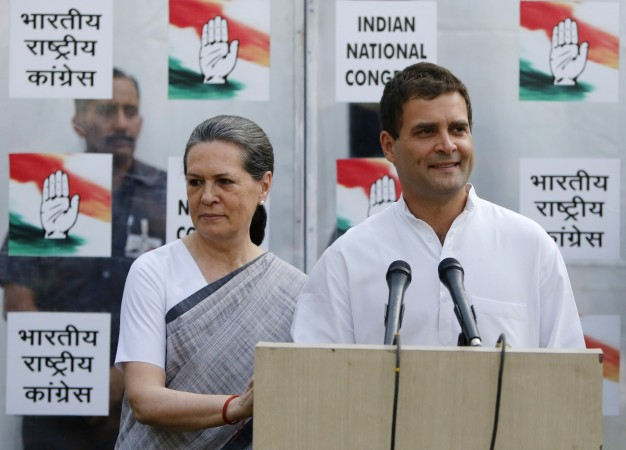 Congress party vice-president Rahul speaks to the media as his mother and chief of Congress Sonia looks on during a news conference in New Delhi
