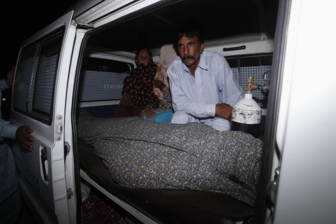 Mohammad Iqbal sits next to his wife Farzana's body, who was killed by family members, in an ambulance outside of a morgue in Lahore