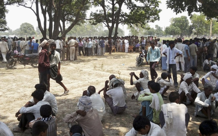 Onlookers at the site where two girls were hanged from tree in Badaun district in Uttar Pradesh