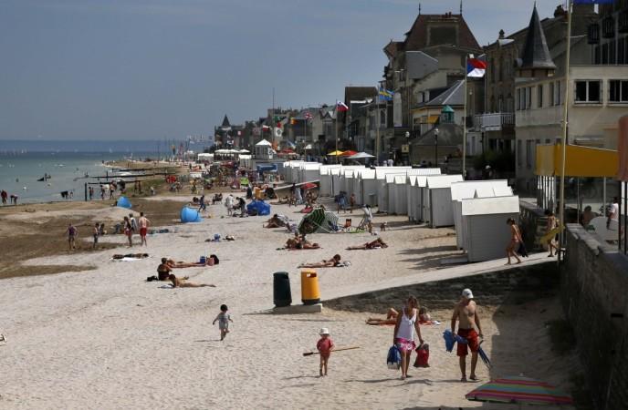 Tourists enjoy the sunshine on the former Juno Beach D-Day landing zone in Saint-Aubin-sur-Mer (Present Day)