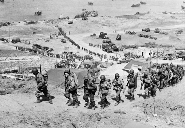 Handout photo of U.S. Army reinforcements marching up a hill past a German bunker after the D-Day landings near Colleville sur Mer