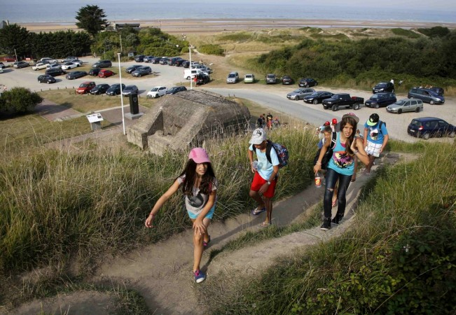Youths hike up a hill past an old German bunker overlooking the former D-Day landing zone of Omaha Beach near Colleville sur Mer