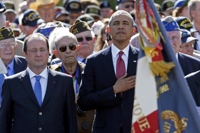 U.S. President Barack Obama and French President Francois Hollande stand with veterans in Colleville-sur-Mer