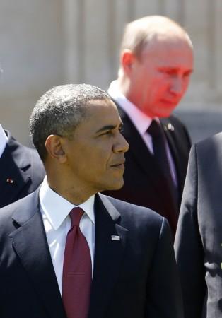 Red light reflected from the carpet illuminates Russian President Vladimir Putin in Benouville