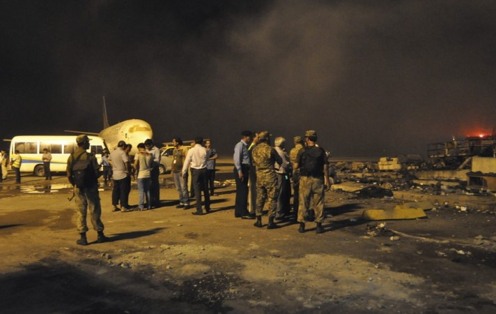 Smoke bellows as security officials and airport staff visit the site damaged by Sunday's Taliban attack on Jinnah International Airport in Karachi