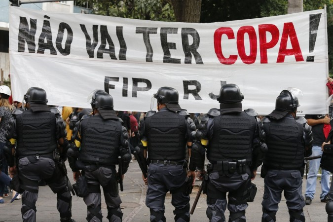 Police officers stand guard in front of a banner during a protest against the 2014 World Cup in Rio de Janeiro