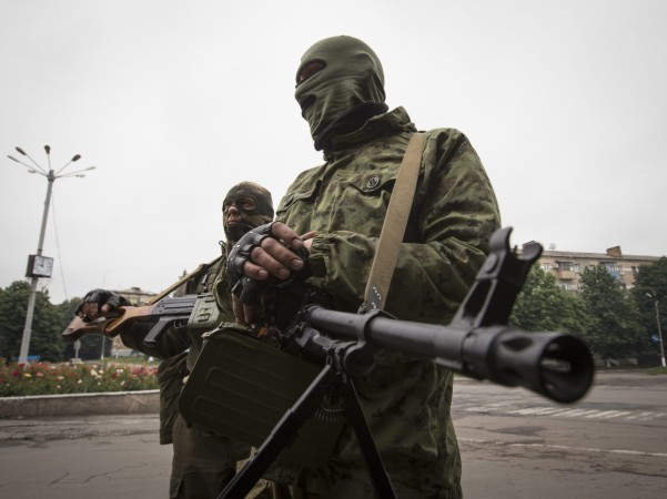 Armed pro-Russian separatists stand at a town center in Snizhnye in eastern Ukraine