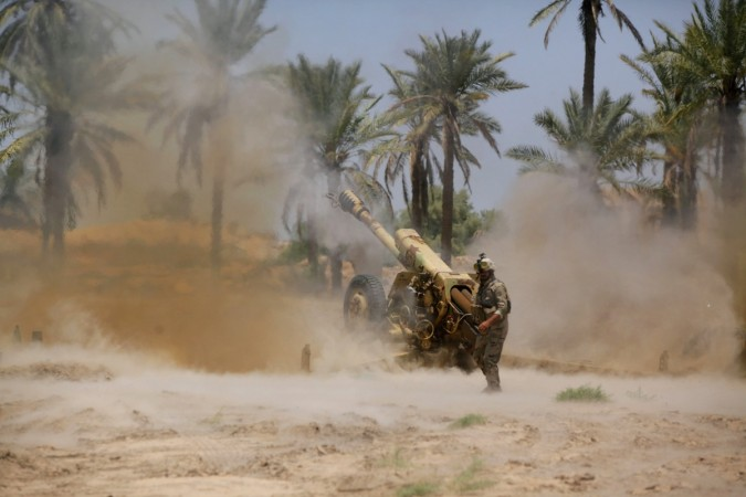 Iraqi security forces fire artillery during clashes with Sunni militant group Islamic State of Iraq and the Levant in Jurf al-Sakhar