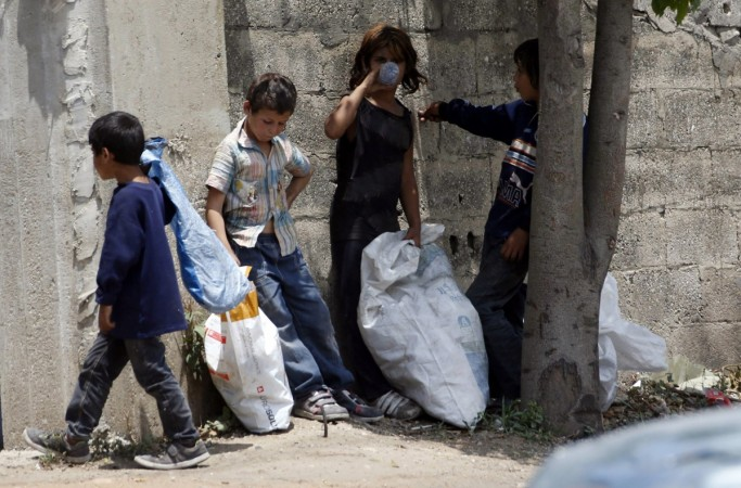 Syrian refugee children collect plastics as they stand along a street in south of Sidon