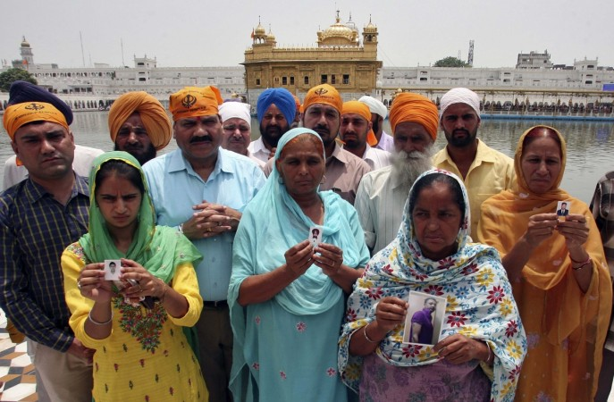 Relatives pose with the photographs of Indian workers, who have been kidnapped in Iraq, in front of the holy Sikh shrine, the Golden Temple, in Amritsar