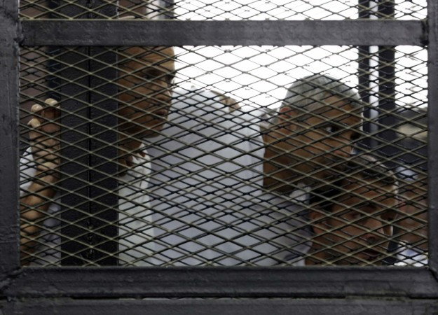 Peter Greste, Mohamed Fahmy and Baher Mohamed listen to the ruling at a court in Cairo