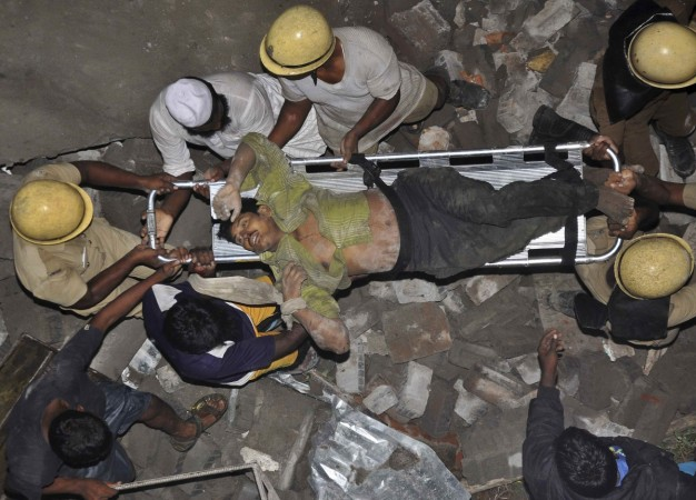 Rescue workers carry an injured man at the site of a collapsed 11-storey building that was under construction on the outskirts of the southern Indian city of Chennai
