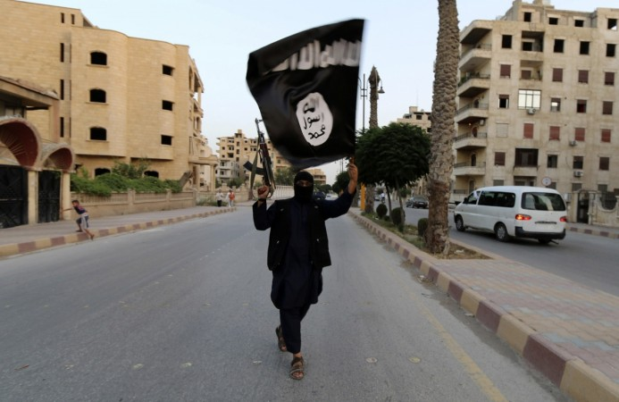 A member loyal to the ISIS waves the flag in Raqqa