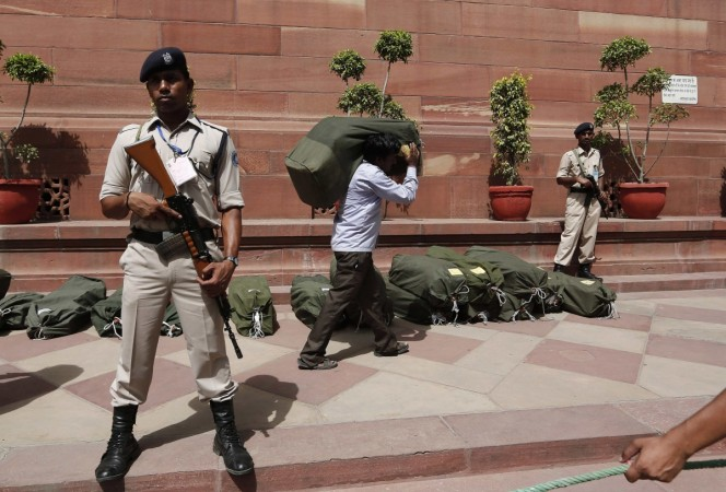 Indian security personnel stand guard near sacks containing the papers of the federal budget for the 2014, 2015 fiscal year, at the parliament in New Delhi