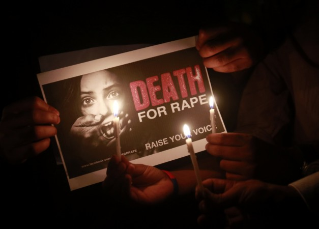 People hold a placard during a candlelight vigil in support of 'Nirbhaya'
